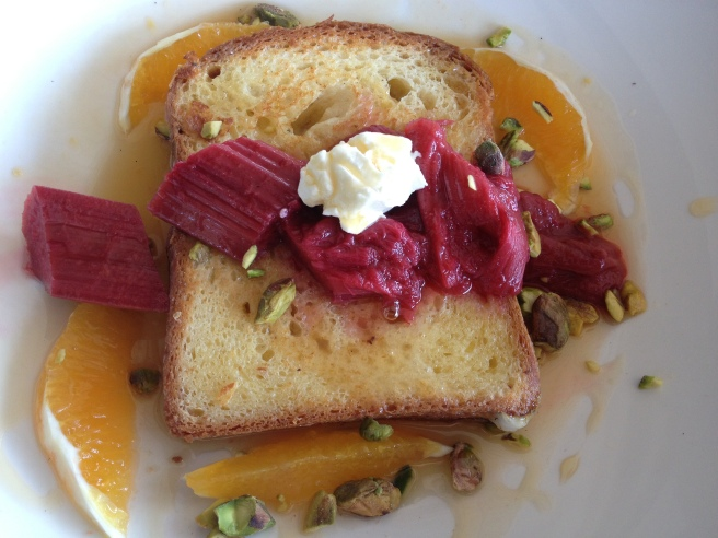 Brioche French toast with vanilla poached rhubarb and fresh orange segments topped with homemade labne and toasted pistachio