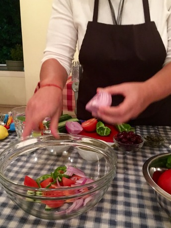 Fofi preparing the horiatiki (traditional Greek salad) - Athens Cooking Lessons